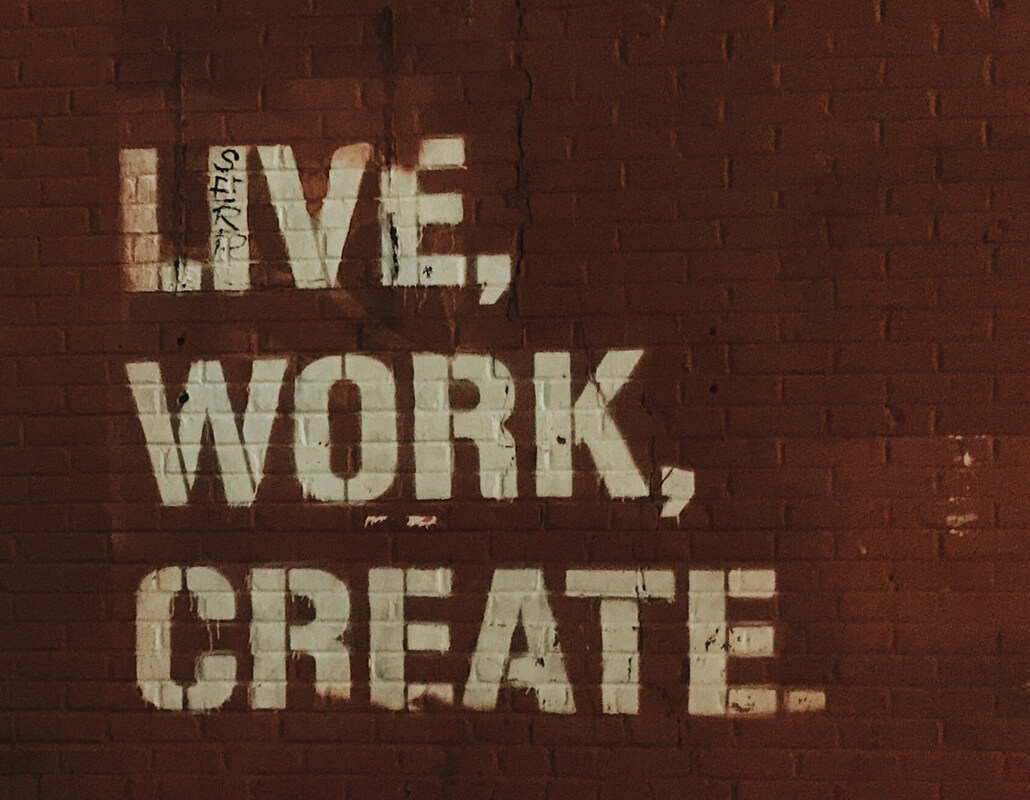 Words Live, Work, Create painted in cream over dark red brick wall