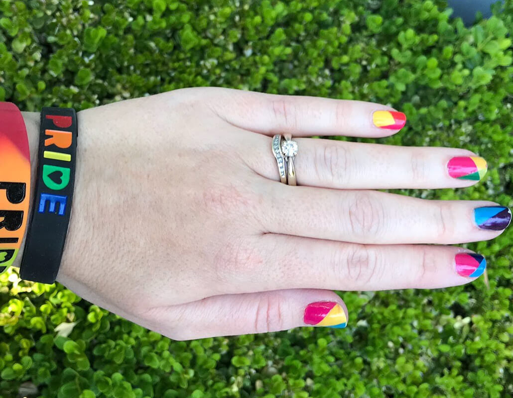 White hand with rainbow painted nails and rainbow bracelets reading pride