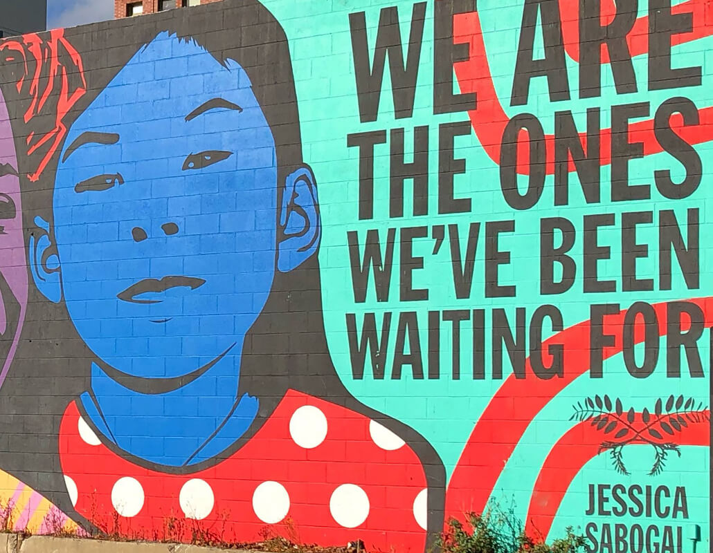 Street art with blue, red, and purple illustrations of young girls and the quote We are the ones we've been waiting for over aqua background