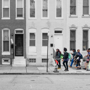 Group of adolescents with lacrosse equipment in color over black and white row houses